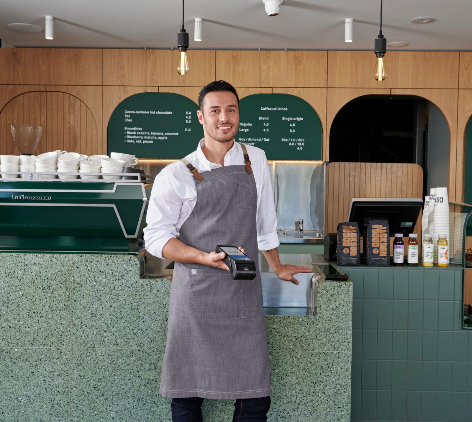 restaurant-owner-holding-black-eftpos-payment-terminal